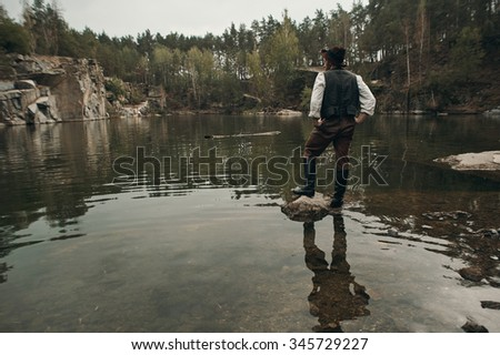 caucasian gold digger in retro clothes standing on rock in lake after hard work. He wears hat, shirt, leather pants, vest and boots.  Sky is cloudy and grey.