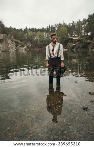caucasian gold digger in retro clothes standing on rock in lake after hard work. He wears shirt, leather pants and boots.  Sky is cloudy and grey.