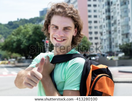 Caucasian guy with bag showing thumb - stock photo