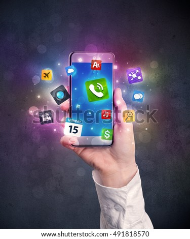 Caucasian hand in business suit holding a smartphone with colorful media icons