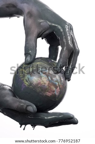 Caucasian hands cupped with black heavy fuel isolated on white background, with a globe in his hand