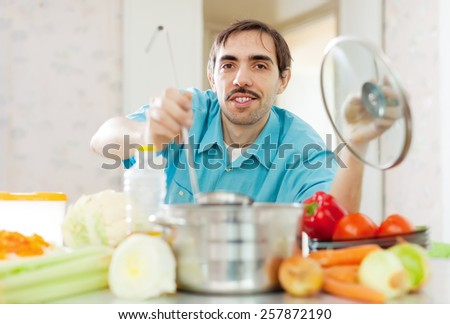 Caucasian handsome man does veggie soup with ladle from pan - stock photo
