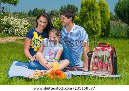 Caucasian happy family - mother, father and daughter having picnic in park.