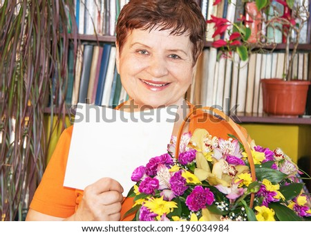 Caucasian happy senior woman with basket of flowers and an empty white post card for your message. Portrait of beautiful female in her 60s at home in the birthday. Copy space, close up, indoor. - stock photo