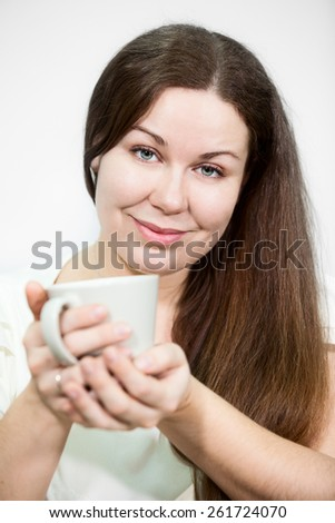 Caucasian happy smiling woman holding tea mug in hands, grey background - stock photo