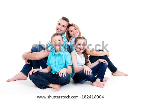 Caucasian happy smiling young family with two children sitting on the floor - stock photo