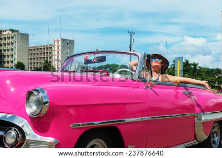 Caucasian, happy woman with arms outstretched in the pink cabriolet, convertible car - stock photo