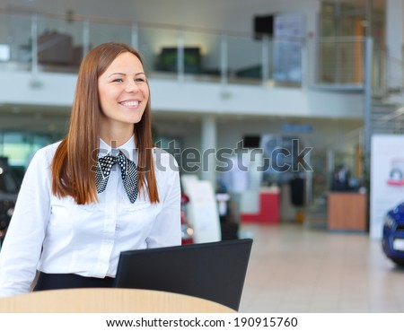 Caucasian happy woman working as a professional receptionist in shop selling cars - stock photo