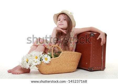 Caucasian happy young girl in a summer dress and a hat with a basket of white daisies sitting near vintage suitcase for traveling on a white background - stock photo