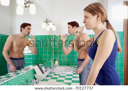 caucasian heterosexual couple brushing teeth together in bathroom and looking at mirror. Horizontal shape, waist up, side view