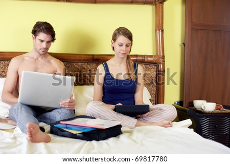 caucasian heterosexual couple working with laptop computer and touch pad in bedroom. Horizontal shape, full length, front view - stock photo