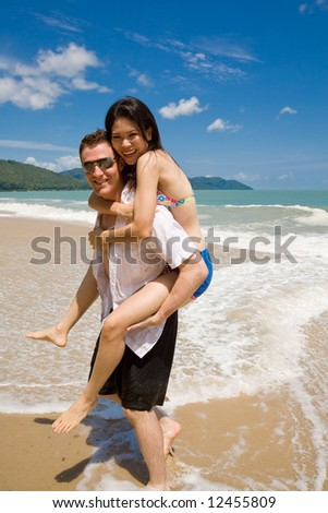 caucasian hunk carrying a gorgeous asian woman on his back having lots of fun