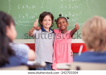 Caucasian kid and afro american female smiling to the classroom in front of chalkboard. Primary school concept. - stock photo