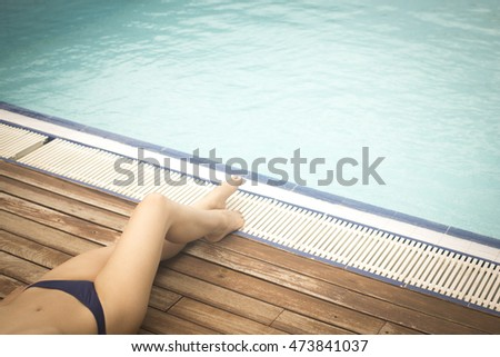 caucasian lady sunbathing in bikini in summer by outdoors swimming pool on wooden sundeck terrace.