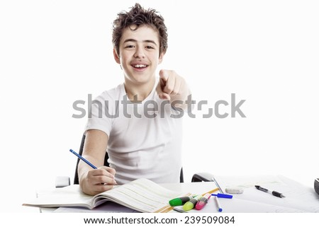 Caucasian Latin Teenager boy sitting while doing homework is happy and smiles pointing his index finger to viewers and writing with pencil - stock photo