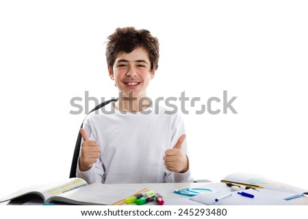 Caucasian latin young boy sits in front of homework, smiles  and feels happy  showing success thumbs up sign with both hands - stock photo