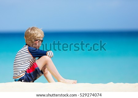 caucasian little boy in swimsuit enjoying beach vacation at anguilla island, perfect caribbean beach, sun protection concept, copy space on side