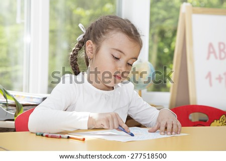 Caucasian little girl drawing with pencils sitting at the table in the nursery  - stock photo