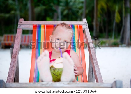 Caucasian little girl drinking coconut milk on the beach sitting in the sunbed - stock photo