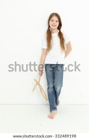 Caucasian little girl holding wooden toy figure man - stock photo