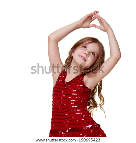 Caucasian little girl in a shiny red dress dancing