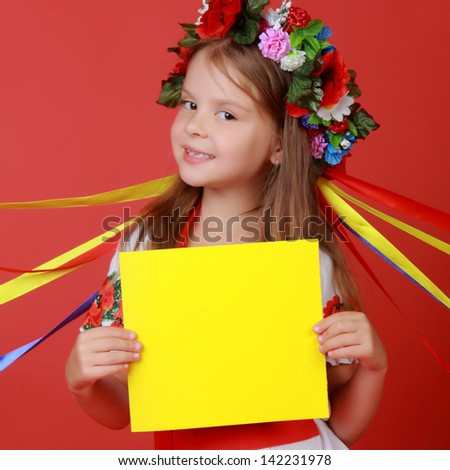 Caucasian little girl is holding yellow blank sheet against bright red background/Cute child in a traditional costume on Holiday - stock photo