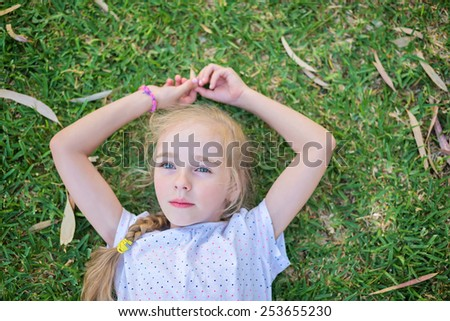 Caucasian little girl lay on green grass, top view - stock photo