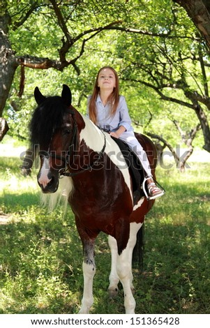 Caucasian little girl riding her pony in the beautiful summer garden/Charming horse is eating green grass meadow