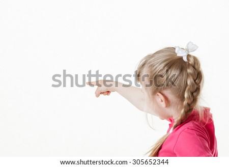 Caucasian little girl turning back and indicating something , white background - stock photo