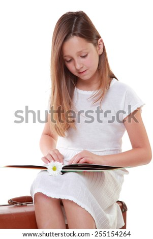 Caucasian little girl with beautiful hair in a white dress is reading a book while sitting on a suitcase isolated on white - stock photo