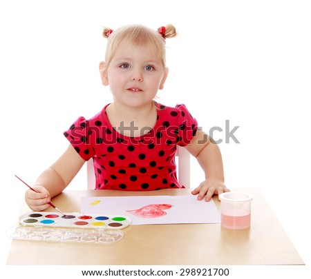 Caucasian little girl with blond hair braided in pigtails in a red polka dot dress sitting at the table and paints with watercolors on a white sheet of paper , the girl is in kindergarten-Isolated on - stock photo