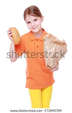 caucasian little girl with buns/little girl offers tasty bun - stock photo