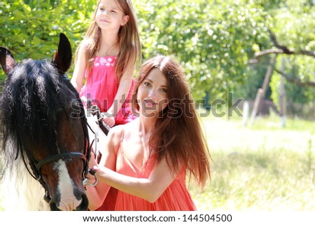 Caucasian little girl with her mother learns to ride a horse in a summer apple garden - stock photo
