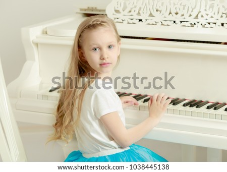 Caucasian little girl with long blond hair, in a beautiful pink skirt and white T-shirt and a pink bow on her chest.She plays music with the piano.