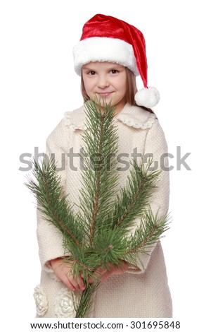 caucasian little girl with long hair in red Santa hat holding a bush natural pine on white background/Emotional child in Santa's hat is happy and laughing with Christmas tree - stock photo