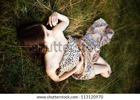 Caucasian long hair girl in spotty dress  lying on the ground.