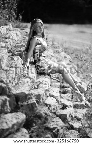 Caucasian long hair model in dress sitting on stones. Black&white picture. - stock photo