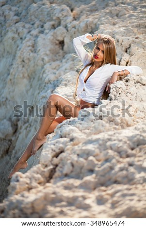 Caucasian long hair model posing in red bikini and white shirt on stones. - stock photo