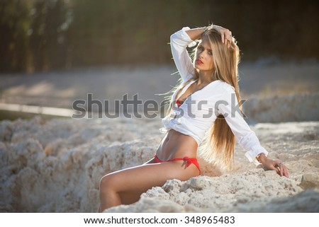 Caucasian long hair model posing in red bikini and white shirt on stones.