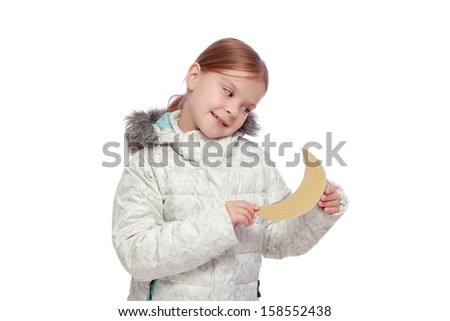 Caucasian lovely little girl in a white winter down jacket keeps the moon on a white background