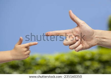 caucasian male and boy hand pointing, or gun gesture, on blurred natural green and blue sky background - stock photo