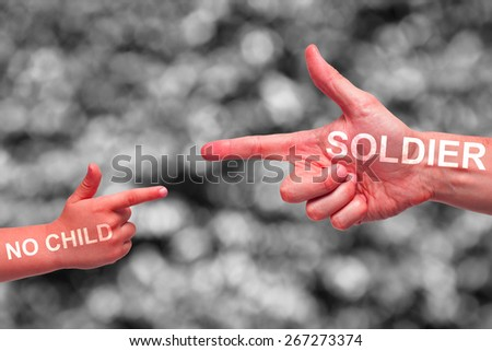 Caucasian male and boy painted red hands pointing, or gun gesture, on blurred black and white background. No Child Soldier campaign text. - stock photo