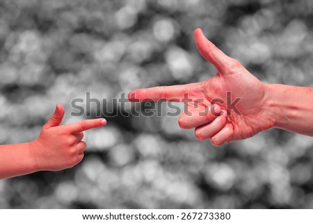 Caucasian male and boy painted red hands pointing, or gun gesture, on blurred black and white background. - stock photo