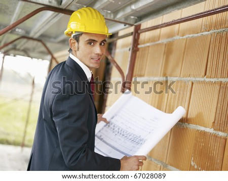 Caucasian male architect holding blueprints and looking at camera. Horizontal shape, side view, waist up