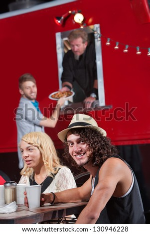 Caucasian male at table with friends ordering pizza - stock photo