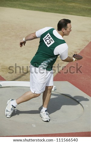 Caucasian male athlete preparing to throw a discus - stock photo
