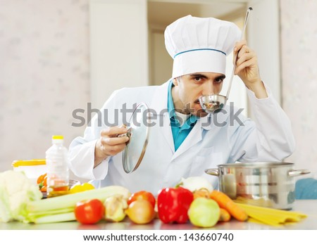 Caucasian male chef tasting soup with ladle from pan in kitchen - stock photo