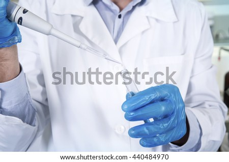 Caucasian male chemist scientific researcher in medical mask, blue rubber gloves and white coat using test tubescultivating whit inoculation loops in pipette at his workplace in the laboratory. - stock photo