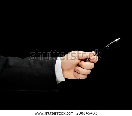 Caucasian male hand in a business suit, holding the pen, low-key lighting composition, isolated over the black background