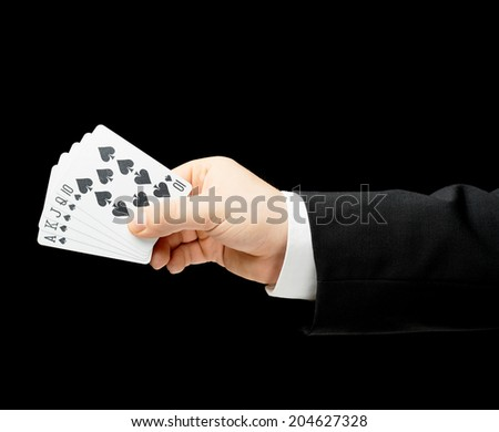 Caucasian male hand in a business suit, holding the royal flush poker combination, low-key lighting composition, isolated over the black background - stock photo